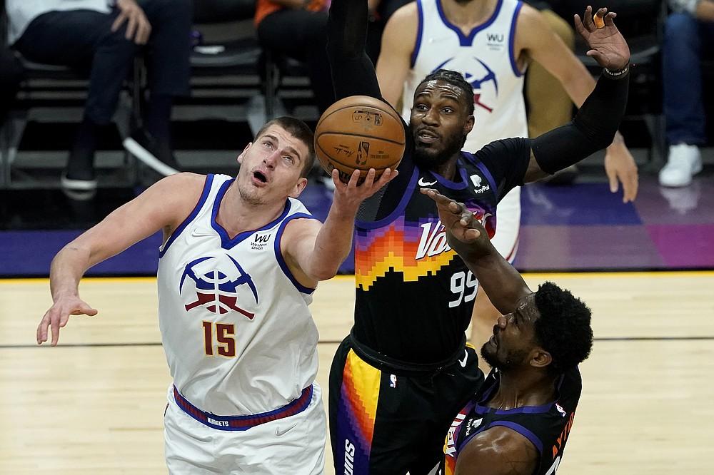 Denver Nuggets center Nikola Jokic (15) shoots as Phoenix Suns forward Jae Crowder (99) defends during the first half of Game 2 of an NBA basketball second-round playoff series, Wednesday, June 9, 2021, in Phoenix. (AP Photo/Matt York)