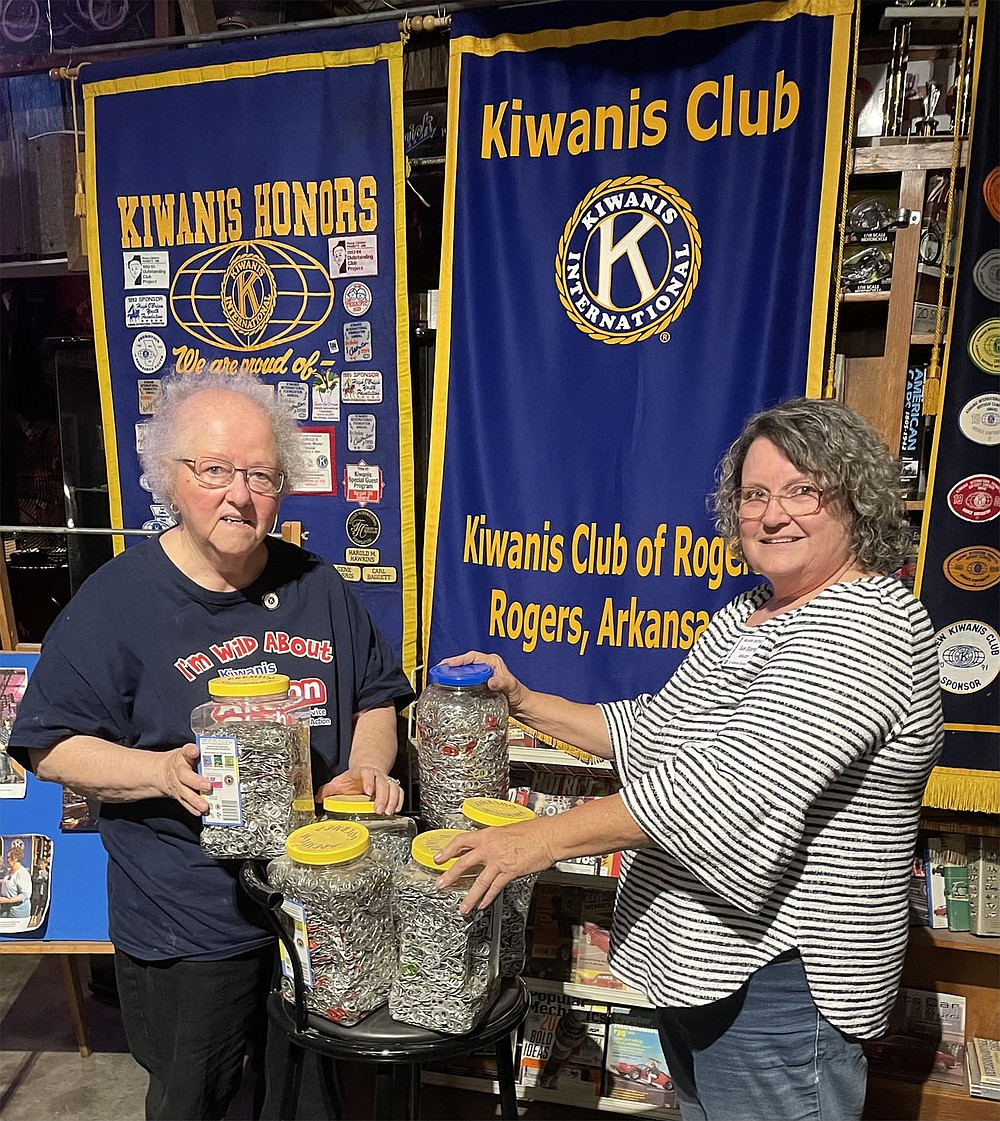 """Sue Storey, Rogers Kiwanis, pound gallons of """"pop tops"""" to Dolores Stamps for ERC Northwest Arkansas Aktion Club Springdale.  Club Aktion members have been accumulating spinning tops to support the ARKOMA Ronald McDonald House Charities association for eleven years."""