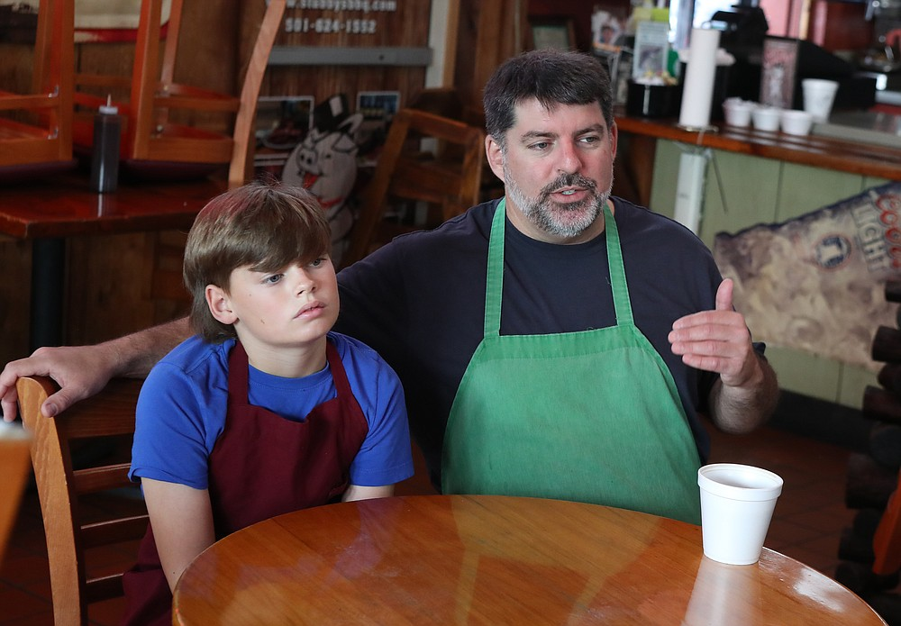 Palmer Dunkel, left, is growing up in the family business much like his father Chris Dunkel, right, did at Stubby's BBQ. - Photo by Richard Rasmussen of The Sentinel-Record