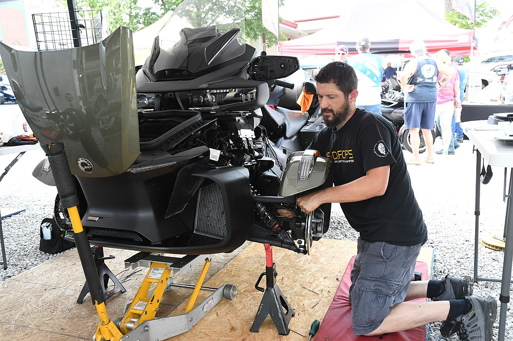 Aaron Hand, of Spyderpops, works on a Spyder at the Spyder rally behind the Best Western Winners Circle on the first day of the three-day rally. - Photo by Tanner Newton of The Sentinel-Record