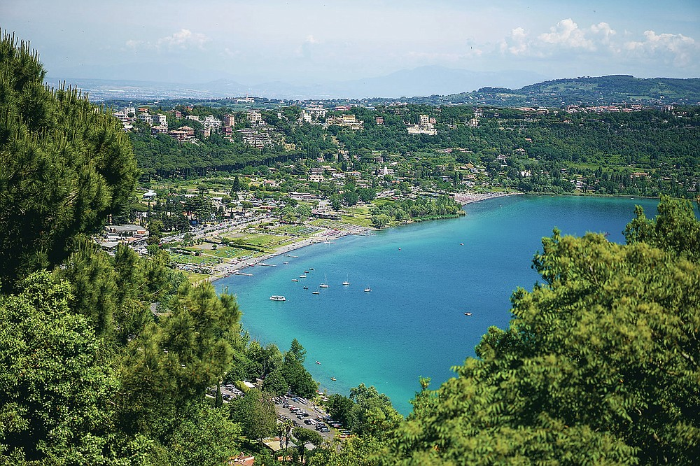 A view of the Albano lake as seen from the gardens of the Papal Palace in Castel Gandolfo, some 30 kilometers southeast of Rome, Saturday, May 29, 2021. As Covid-19 restrictions are slowly being lifted in Italy, thousands of people are returning to visit the extensive gardens and apartments at the Papal Palace of Castel Gandolfo in the Alban Hills near Rome, that for hundreds of years have been the summer retreat for Popes seeking to escape the suffocating heat of Rome. (AP Photo/Andrew Medichini)