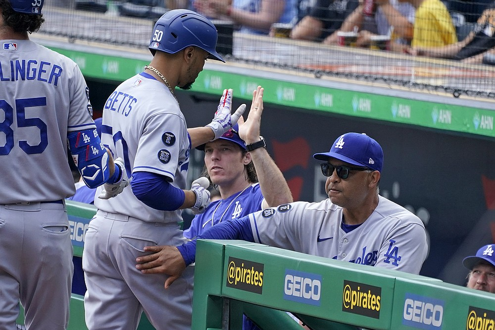 Los Angeles Dodgers' Mookie Betts, center, is greeted at the dugout steps by manager Dave Roberts, right, after hitting a solo home run during the first inning of a baseball game in Pittsburgh, Thursday, June 10, 2021. (AP Photo/Gene J. Puskar)