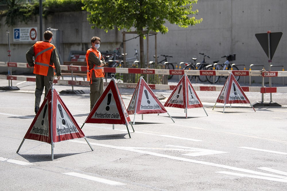 """Members of the civil protection block access to a street in order to install fences outside the Parc La Grange aux Eaux-Vives in Geneva, Switzerland, Wednesday, June 09, 2021. The """"Villa La Grange"""" is the possible but yet unconfirmed venue of the meeting between US president Joe Biden and Russian presidents Vladimir Putin in Geneva, scheduled on Wednesday June 16, 2021. (Martial Trezzini/Keystone via AP)"""