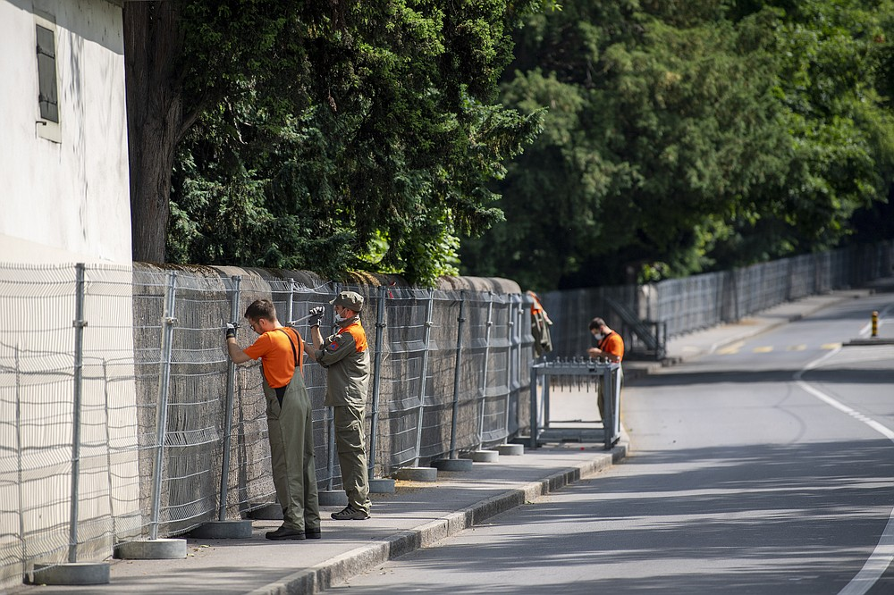 """Members of the civil protection install fences outside the Parc La Grange at the Eaux-Vives in Geneva,, Switzerland, Wednesday, June 09, 2021. The """"Villa La Grange"""" is the possible but yet unconfirmed venue of the meeting between US president Joe Biden and Russian presidents Vladimir Putin in Geneva, scheduled on Wednesday June 16, 2021.  (Martial Trezzini/Keystone via AP)"""