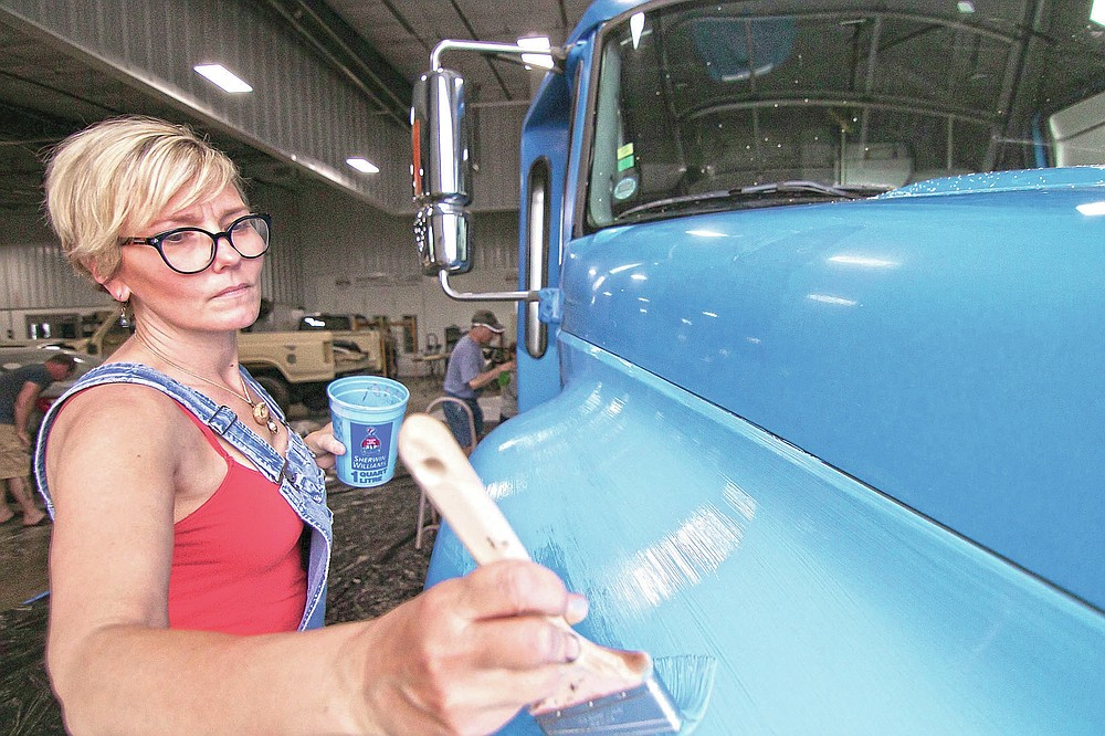 Kelley DeCoste, vice president of a non-profit art initiative called Raw Artwork, works with a team of artists painting a mural on a bus to be used by the Howell Conference and Nature Center for education, in Marion Township, Mich., on Saturday, May 22, 2021. (Gillis Benedict/Livingston County Daily Press & Argus via AP)