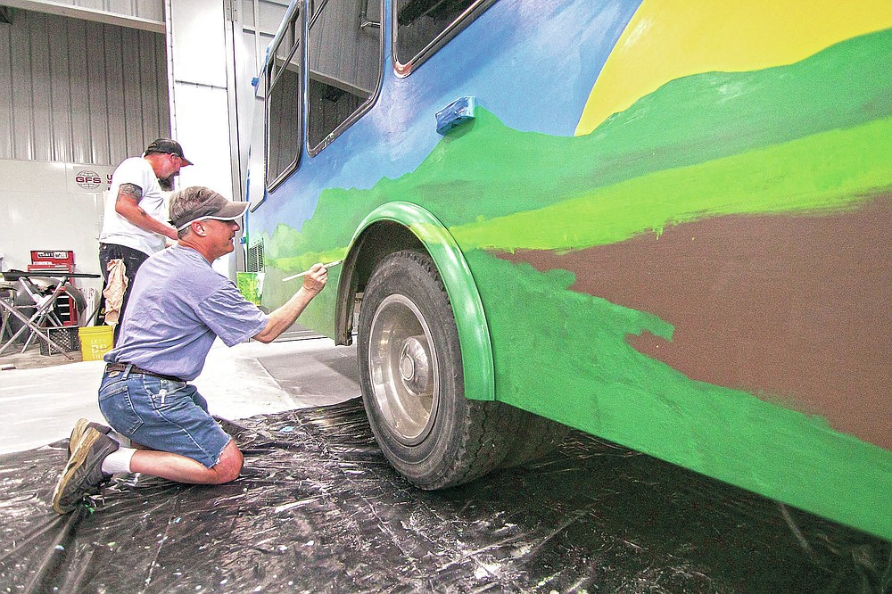 Stacy Karnes, left, and Michael Monroe work on a mural being painted on a bus to be used at the Howell Conference and Nature Center for education, in Marion Township, Mich., on Saturday, May 22, 2021. The effort is part of Raw Artwork's non-profit initiative to provide maker spaces of artwork. (Gillis Benedict/Livingston County Daily Press & Argus via AP)