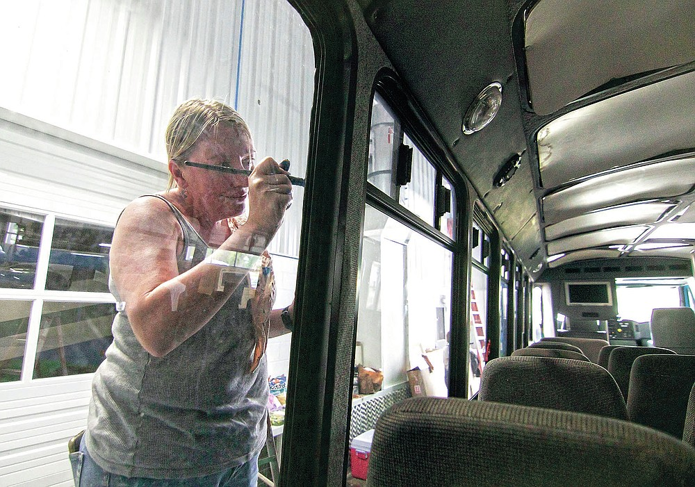 Karrie Martin, one of a number of artists comprising the Raw Artwork initiative, paintw a mural on the exterior of a Howell Conference and Nature Center bus inside Schroeder Auto & RV repair in Marion Township, Mich., on Saturday, May 22, 2021. (Gillis Benedict/Livingston County Daily Press & Argus via AP)
