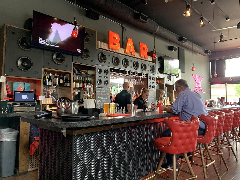 The bar at Rock N Roll Sushi, with an Art Deco facade, is the single surviving relic of the Atlas Bar. Behind the bar, speakers indicate that the management could blow customers out the windows if they ever cranked up the music videos showing on the TV screens. (Arkansas Democrat-Gazette/Eric E. Harrison)