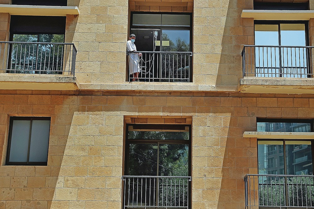 A patient with intravenous machine stands on a balcony at the Lebanese American University Medical Center-Rizk Hospital in Beirut, Lebanon, Thursday, June 10, 2021. Hospitals in Lebanon warned on Thursday that they may be forced to suspend kidney dialysis next week amid severe shortages in supplies needed, the latest manifestation of Lebanon's accelerating financial crisis and collapsing health sector. (AP Photo/Bilal Hussein)