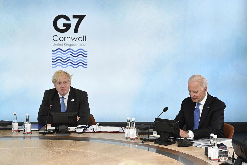 Il primo ministro britannico Boris Johnson, a sinistra, e il presidente degli Stati Uniti Joe Biden siedono attorno al tavolo al vertice della riunione del Gruppo dei Sette, a Carbis Bay, in Cornovaglia, in Inghilterra, venerdì 11 giugno 2021 (Leon Neal/Pool Photo via AP)