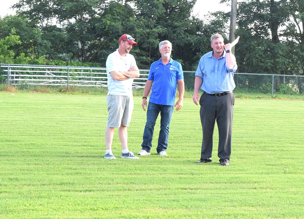 Westside Eagle Observer/MIKE ECKELS Kevin Smith (left), Ike Owens and Steve Watkins stand at midfield of Bulldog Stadium to get an idea of what the new bleachers may look like during a special school board meeting June 9. The board voted to purchase and move a new set of bleachers from old Cardinal Stadium in Farmington to Decatur, replacing the current aging stands.