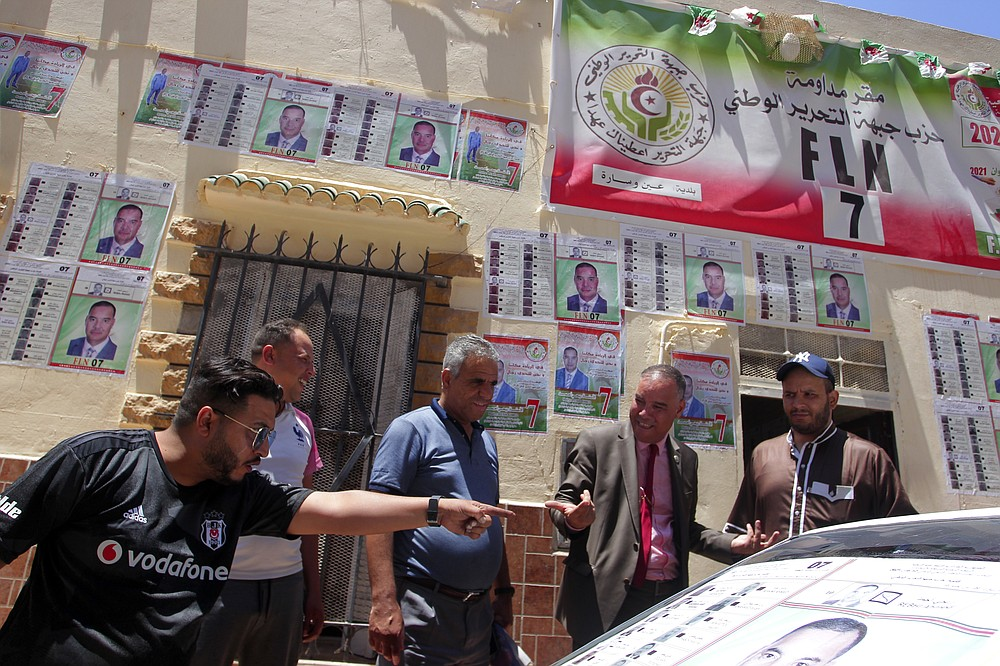 """Men argue by electoral posters in Ain Ouessara, 190 kilometers (118 miles) from Algiers, Thursday, June 10, 2021. In addition to the traditional parties, dozens of independent candidates have decided to take part in the legislative elections on June 12, that the government organized earlier than expected under a new system meant to weed out corruption and open voter rolls — a major step in President Abdelmadjid Tebboune's promise of a """"new Algeria."""" (AP Photo/Fateh Guidoum)"""