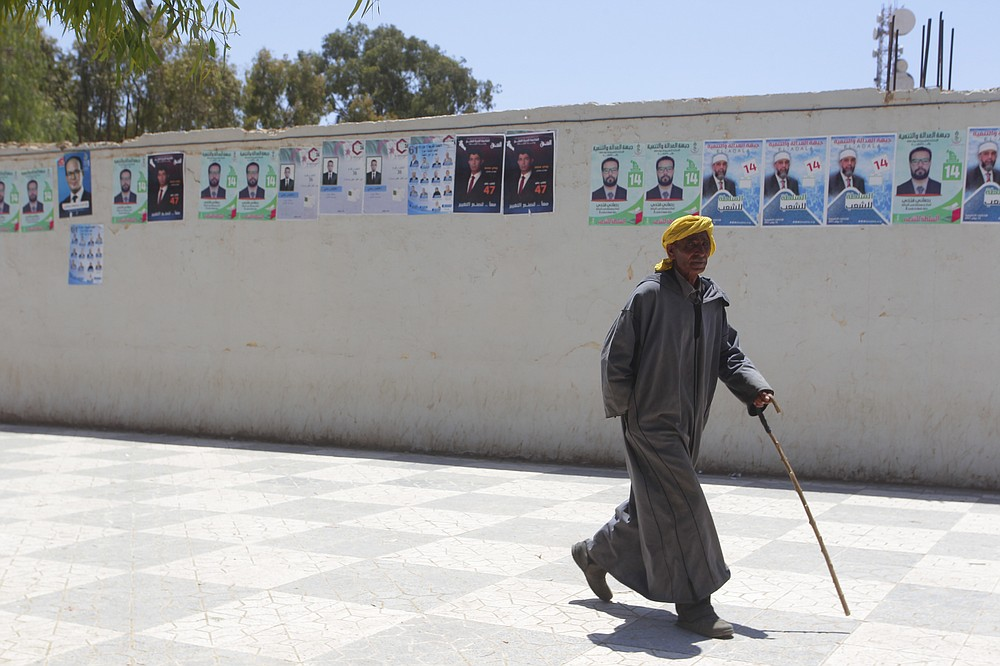 """A man walks past electoral posters in Ain Ouessara, 190 kilometers (118 miles) from Algiers, Thursday, June 10, 2021. In addition to the traditional parties, dozens of independent candidates have decided to take part in the legislative elections on June 12, that the government organized earlier than expected under a new system meant to weed out corruption and open voter rolls — a major step in President Abdelmadjid Tebboune's promise of a """"new Algeria."""" (AP Photo/Fateh Guidoum)"""