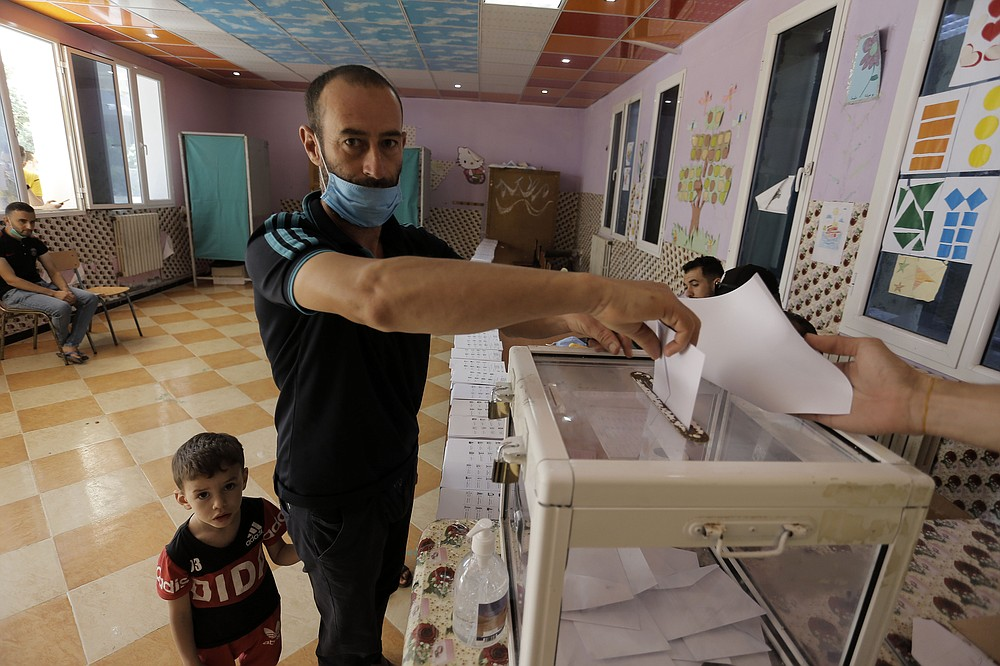 """A man casts his vote in a polling station in the country's first legislative elections sine the ouster of ex-president Bouteflika, in Algiers, Algeria, Saturday, June 12, 2021. Algerians vote Saturday for a new parliament in an election with a majority of novice independent candidates running under new rules meant to satisfy demands of pro-democracy protesters and open the way to a """"new Algeria."""" (AP Photo/Toufik Doudou)"""
