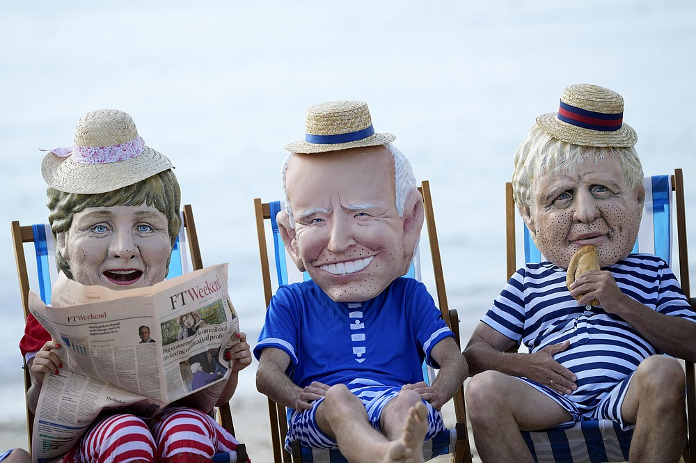Climate activists from Oxfam, wearing giant heads depicting the leaders of the G7, sit on beach chairs as they participate in an action on Swanpool Beach in Falmouth, Cornwall, England, Saturday, June 12, 2021. Leaders of the G7 gather for a second day of meetings on Saturday, in which they will discuss COVID-19, climate, foreign policy and the economy. Leaders depicted from left, German Chancellor Angela Merkel, U.S. President Joe Biden and British Prime Minister Boris Johnson. (AP Photo/Alastair Grant)