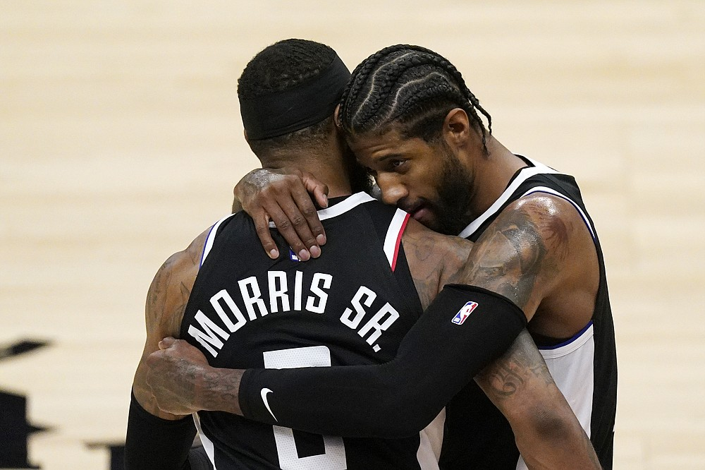 Los Angeles Clippers guard Paul George, right, hugs forward Marcus Morris Sr. during a timeout in the second half of Game 3 of a second-round NBA basketball playoff series against the Utah Jazz Saturday, June 12, 2021, in Los Angeles. (AP Photo/Mark J. Terrill)