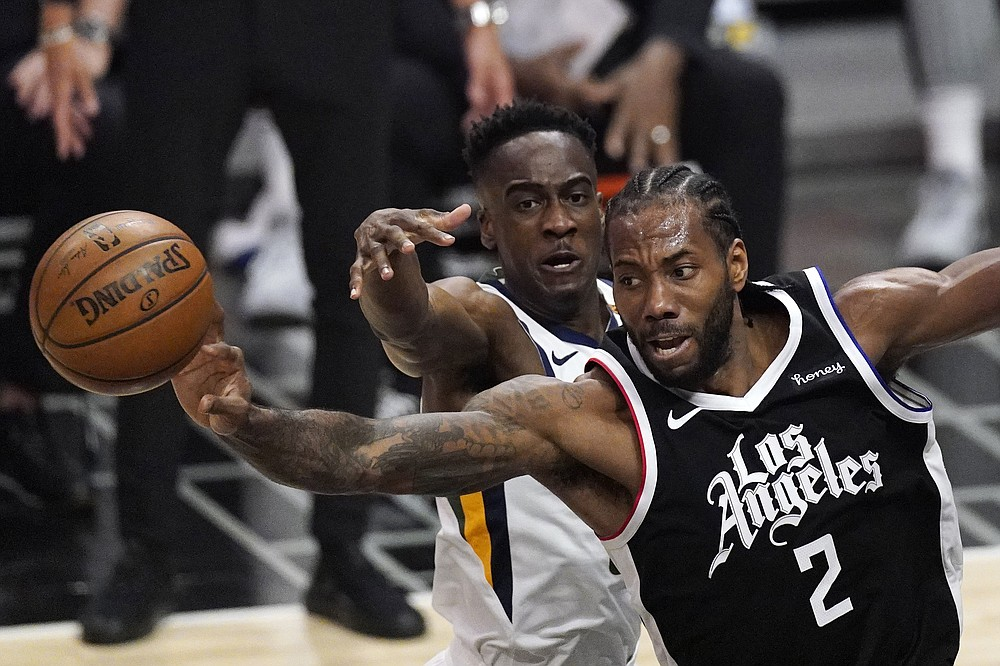 Los Angeles Clippers forward Kawhi Leonard, right, passes the ball while under pressure from Utah Jazz guard Miye Oni during the second half of Game 3 of a second-round NBA basketball playoff series Saturday, June 12, 2021, in Los Angeles. (AP Photo/Mark J. Terrill)
