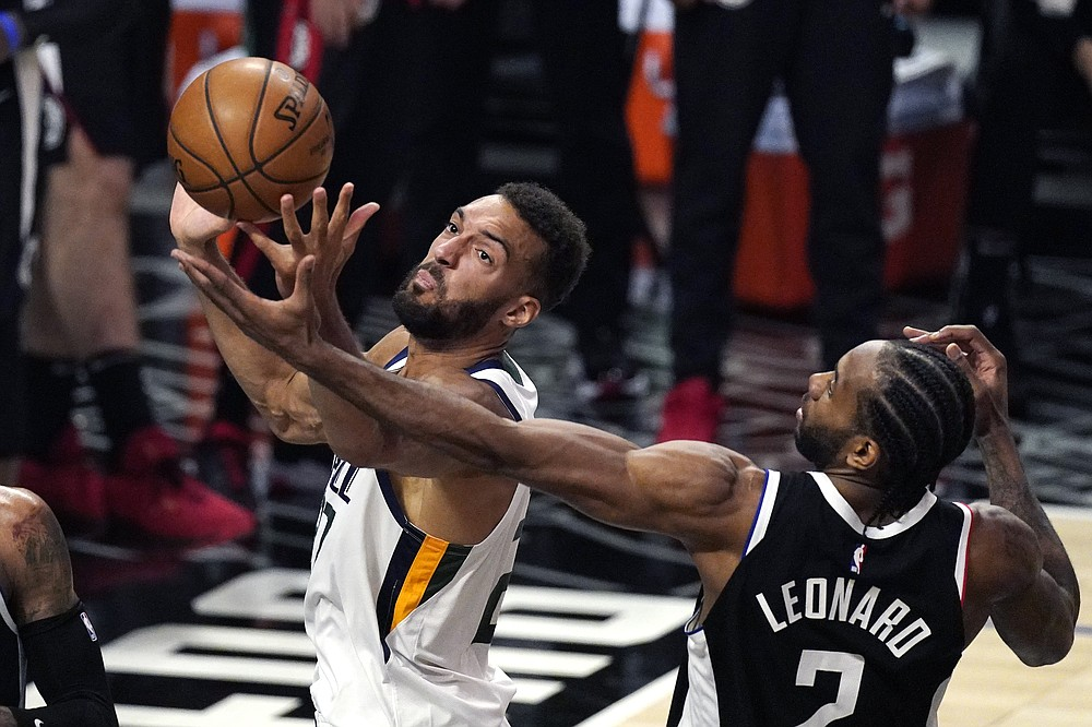 Utah Jazz center Rudy Gobert, left, reaches for a rebound along with Los Angeles Clippers forward Kawhi Leonard during the second half of Game 3 of a second-round NBA basketball playoff series Saturday, June 12, 2021, in Los Angeles. (AP Photo/Mark J. Terrill)