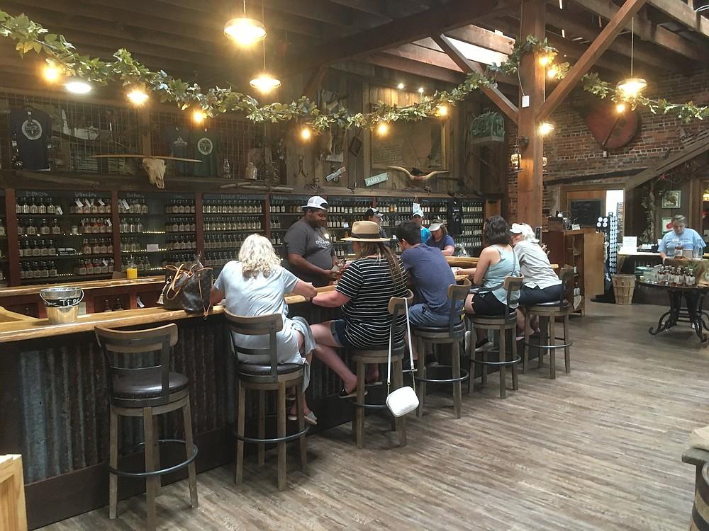 Tory Carrigan serves customers at Crystal Ridge Distillery in Hot Springs, an establishment specializing in 14 varieties of moonshine. (Arkansas Democrat-Gazette/Philip Martin)