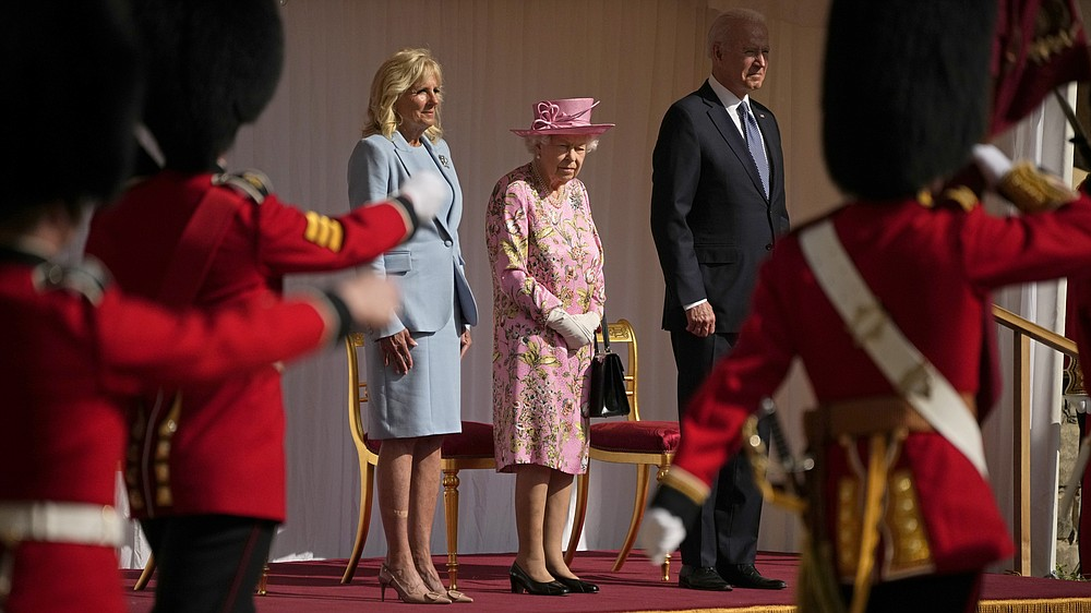 US President Joe Biden and First Lady Jill Biden stand with Britain's Queen Elizabeth II watching a Guard of Honour march past before their meeting at Windsor Castle near London, Sunday, June 13, 2021. (AP Photo/Matt Dunham, Pool)