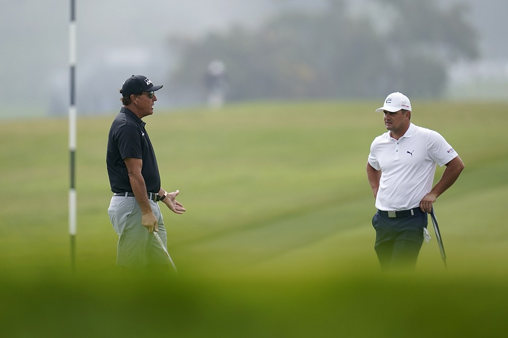 Phil Mickelson, left, talks with Bryson DeChambeau on the 12th hole during a practice round of the U.S. Open Golf Championship Monday, June 14, 2021, at Torrey Pines Golf Course in San Diego. (AP Photo/Gregory Bull)
