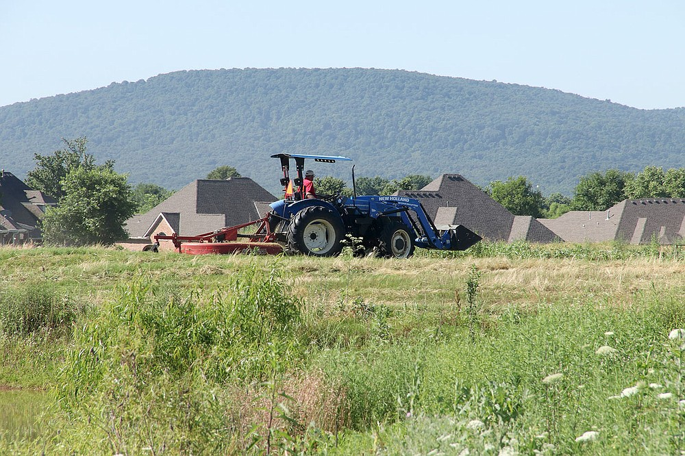 LYNN KUTTER ENTERPRISE-LEADER Floyd Shelley, Farmington public works manager, brush hogs grass at Valley View golf course last week. Three employees spent two days mowing the grass on the property.