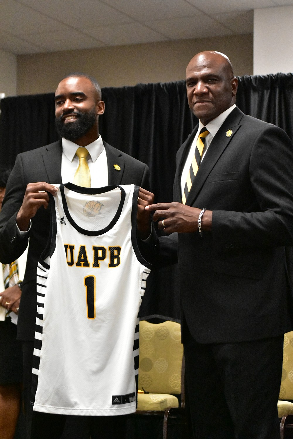 New UAPB men's basketball Coach Solomon Bozeman, left, receives a jersey from recently promoted Athletic Director Chris Robinson at the start of Bozeman's introductory news conference Tuesday. (Pine Bluff Commercial/I.C. Murrell)