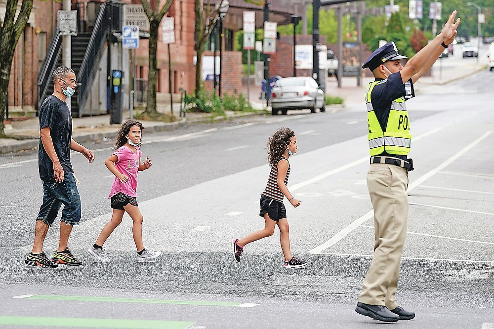 In this Sept. 9, 2020, photo Pedestrians cross an intersection as a cadet in the Baltimore Police Academy directs traffic during an on the field class session in Baltimore. (AP Photo/Julio Cortez)