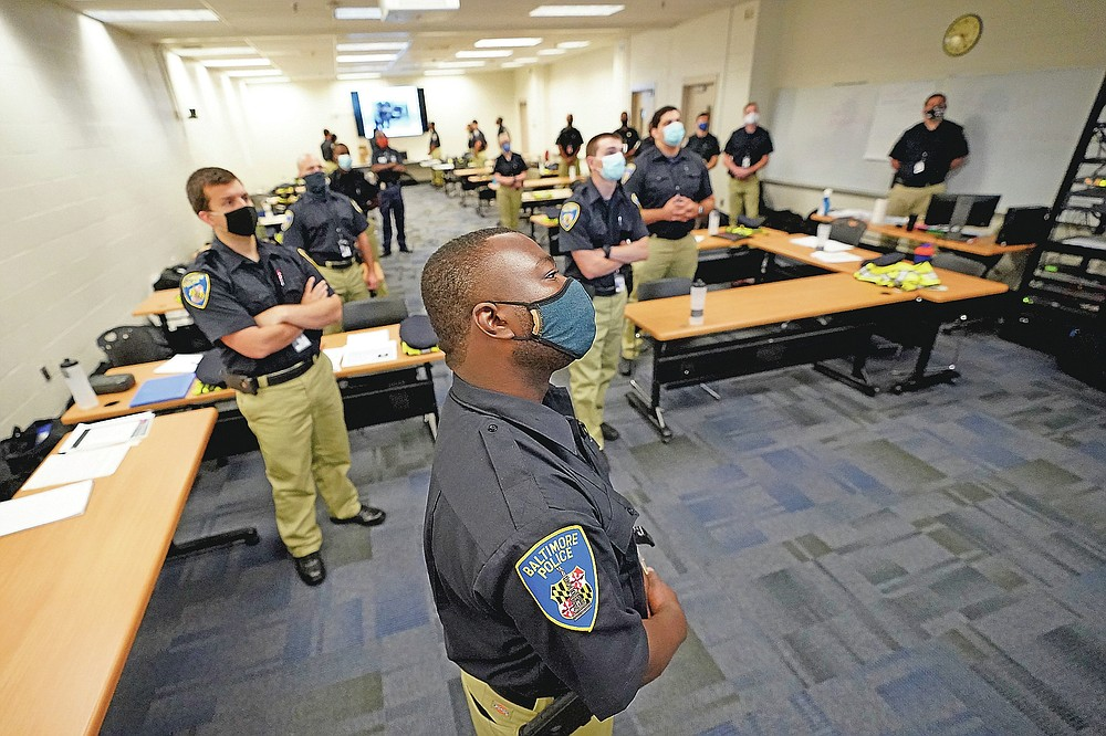 In this Sept. 9, 2020, photo Baltimore Police Academy cadets watch a video presentation during a class session focusing on procedural justice in Baltimore. (AP Photo/Julio Cortez)