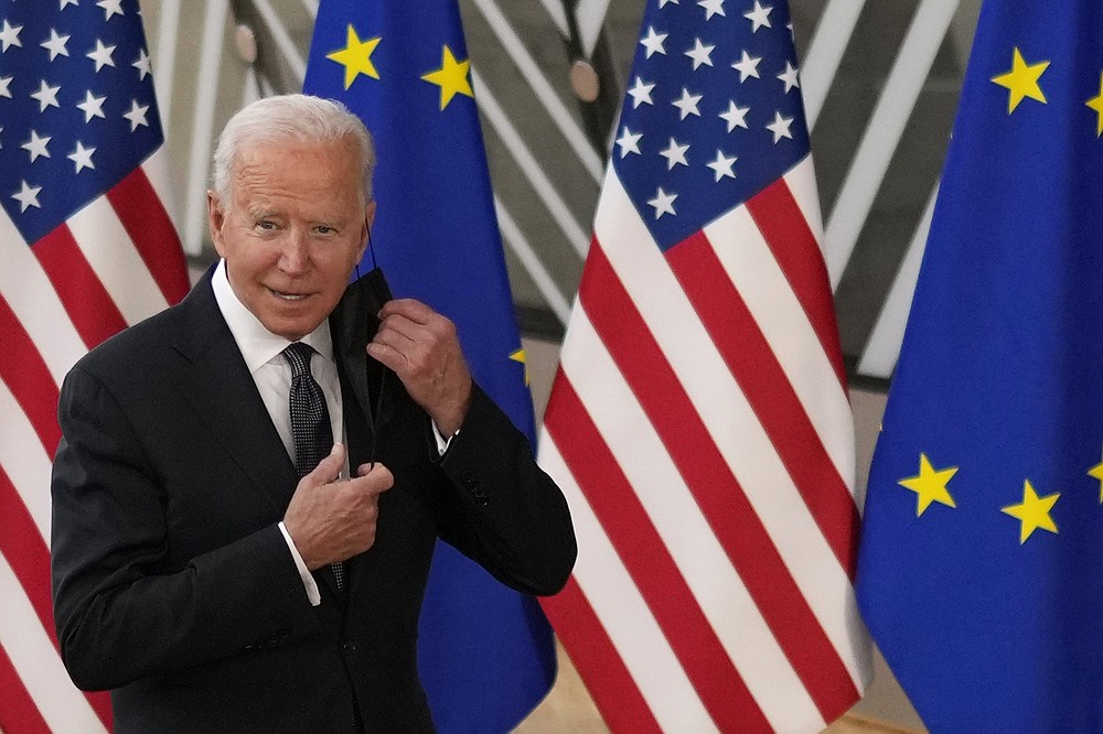 U.S. President Joe Biden takes off his protective facemask prior to speaking with the media during arrival for the EU-US summit at the European Council building in Brussels, Tuesday, June 15, 2021. (AP Photo/Francisco Seco)
