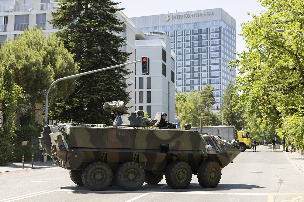 An armored vehicle and a truck block roadway access to the Inter Continental hotel before the arrival of United States President Joe Biden, Tuesday, June 15, 2021, in Geneva, Switzerland. The meeting between US President Joe Biden and Russian President Vladimir Putin is scheduled in Geneva for Wednesday, June 16. (Cyril Zingaro/Keystone via AP)