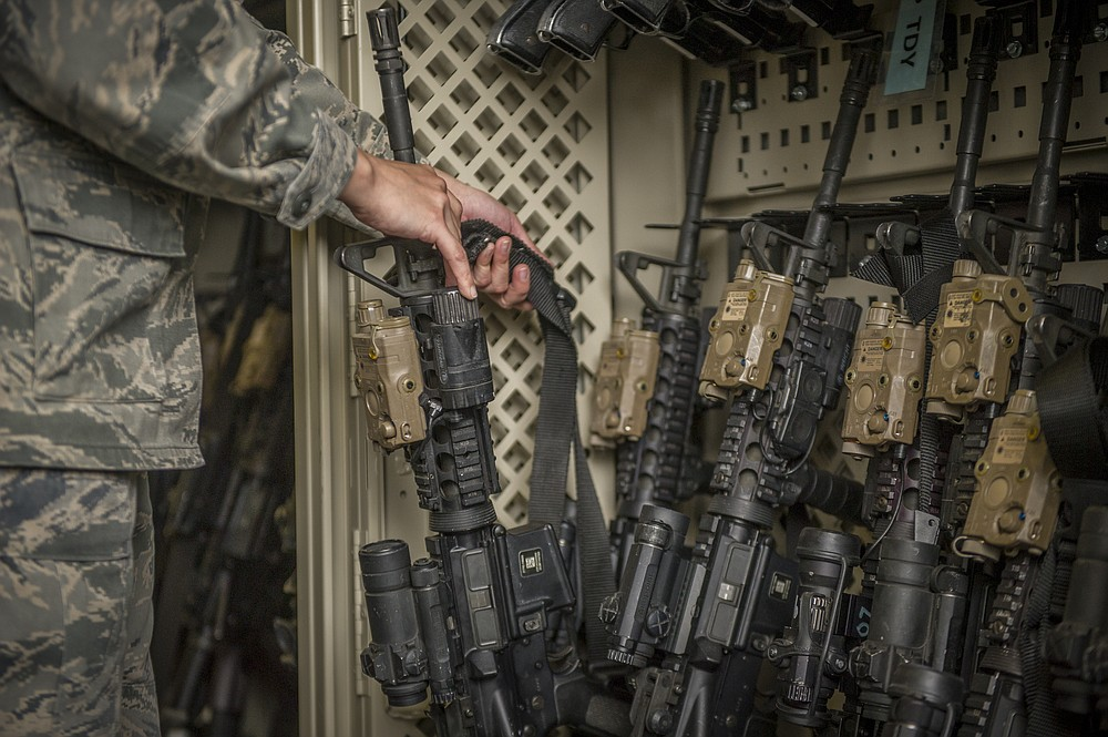 In this April 2, 2015, photo made available by the U.S. Air Force, a senior airman from the 49th Security Forces Squadron in charge of the armory,  returns an M4 carbine to a rack at Holloman Air Force Base, N.M. The Pentagon used to share annual updates about missing weapons with Congress, but that requirement ended and, with it, public accountability has slipped. The Army and Air Force couldn't readily tell AP how many weapons they were missing from 2010 through 2019. (Airman 1st Class Aaron Montoya/U.S. Air Force via AP)