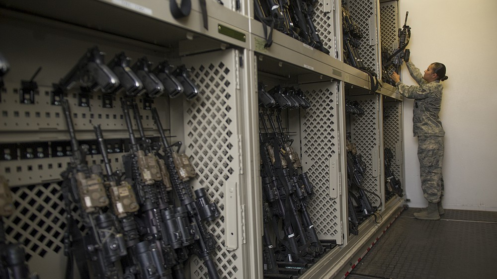 In this April 2, 2015, photo made available by the U.S. Air Force, a senior airman from the 49th Security Forces Squadron in charge of the armory returns an M4 carbine to a rack at Holloman Air Force Base, N.M. Using government records covering the Army, Marines, Navy and Air Force, an Associated Press investigation showed that military pistols, machine guns, shotguns and assault rifles vanished from armories, supply warehouses, Navy warships, firing ranges and other places where they were used, stored or transported. (Airman 1st Class Aaron Montoya/U.S. Air Force via AP)