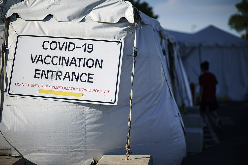 A person arrives for a COVID-19 inoculation at a mass-vaccination site at the former Citizens Bank headquarters in Cranston, R.I., Thursday, June 10, 2021. The U.S. death toll from COVID-19 has topped 600,000, even as the vaccination drive has drastically slashed daily cases and deaths and allowed the country to emerge from the gloom. (AP Photo/David Goldman)