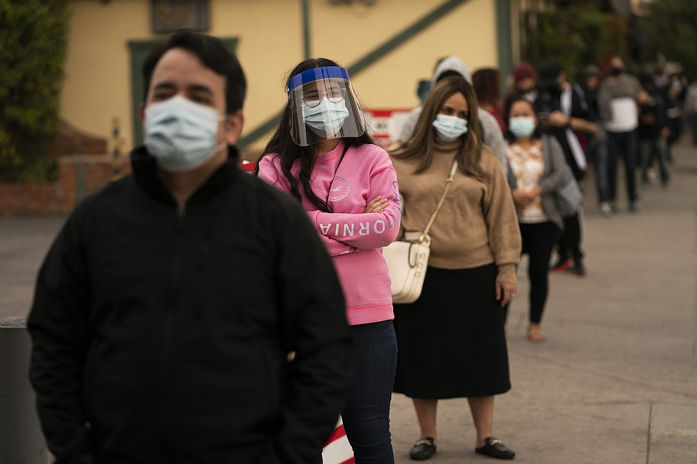 FILE - In this Monday, Dec. 7, 2020, file photo, people wait in line for COVID-19 testing at a site operated by CORE in Los Angeles. Virtually every state is reporting surges in cases and deaths. The U.S. death toll from COVID-19 has topped 600,000, even as the vaccination drive has drastically slashed daily cases and deaths and allowed the country to emerge from the gloom. (AP Photo/Jae C. Hong, File)