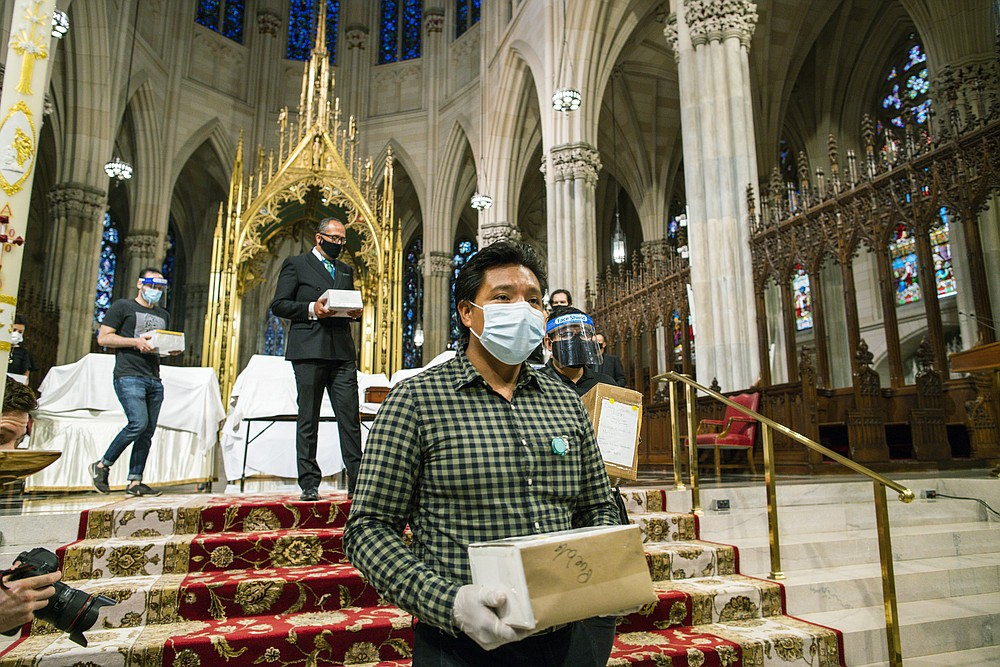 FILE - In this July 11, 2020, file photo, mourners carry the remains of loved ones following the blessing of the ashes of Mexicans who died from COVID-19 at St. Patrick's Cathedral in New York. The U.S. death toll from COVID-19 has topped 600,000, even as the vaccination drive has drastically slashed daily cases and deaths and allowed the country to emerge from the gloom. (AP Photo/Eduardo Munoz Alvarez, File)