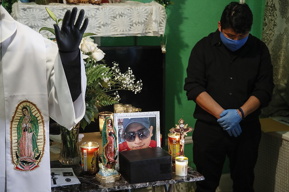 FILE - In this May 9, 2020, file photo, the Rev. Fabian Arias, left, performs an in-home service beside the remains of Raul Luis Lopez who died from COVID-19 the previous month as Lopez's cousin Miguel Hernandez Gomez, right, bows his head in prayer in the Corona neighborhood of the Queens borough of New York. (AP Photo/John Minchillo, File)
