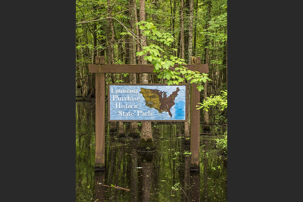 A sign standing in water ushers visitors into Louisiana Purchase Historic State Park near Brinkley. (Arkansas Democrat-Gazette/Cary Jenkins)