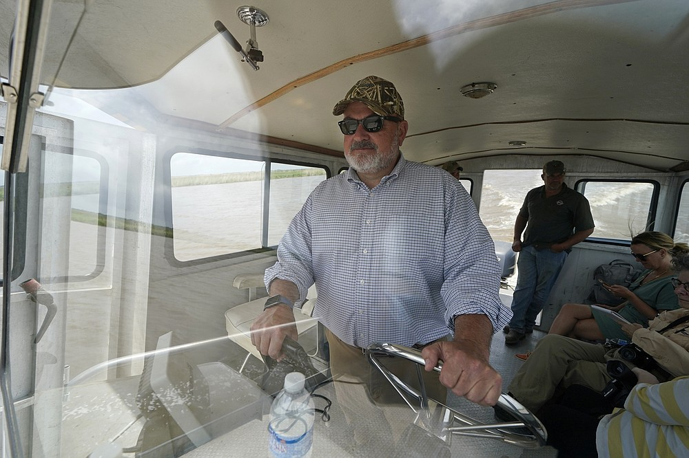 Harold Osborn, great-great-grandson of the McIlhenny Co.'s founder, pilots a boat as he tours the wetlands with employees and The Associated Press, on Avery Island, La., where Tabasco brand pepper sauce is made, Tuesday, April 27, 2021. As storms grow more violent and Louisiana loses more of its coast, the family that makes Tabasco Sauce is fighting erosion in the marshland that buffers it from hurricanes and floods. Overall, it's probably a standoff, says CEO and president Osborn.  (AP Photo/Gerald Herbert)