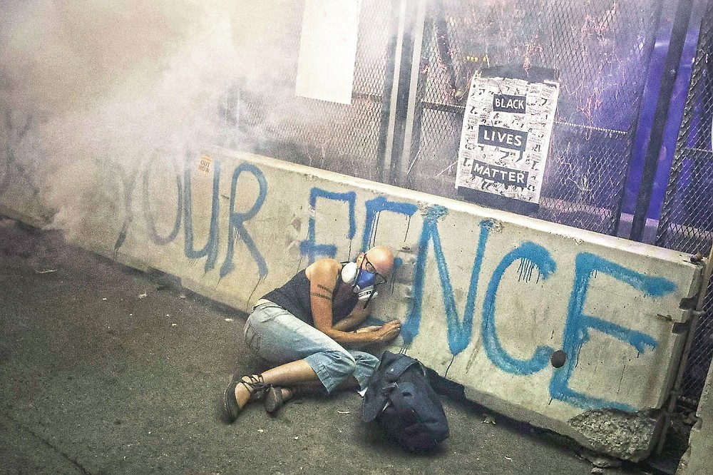 A demonstrator hides under a barrier as federal officers release tear gas during a Black Lives Matter protest at the Mark O. Hatfield United States Courthouse, July 29, 2020, in Portland, Ore. The image was part of a series of photographs by The Associated Press that won the 2021 Pulitzer Prize for breaking news photography. (AP Photo/Marcio Jose Sanchez)