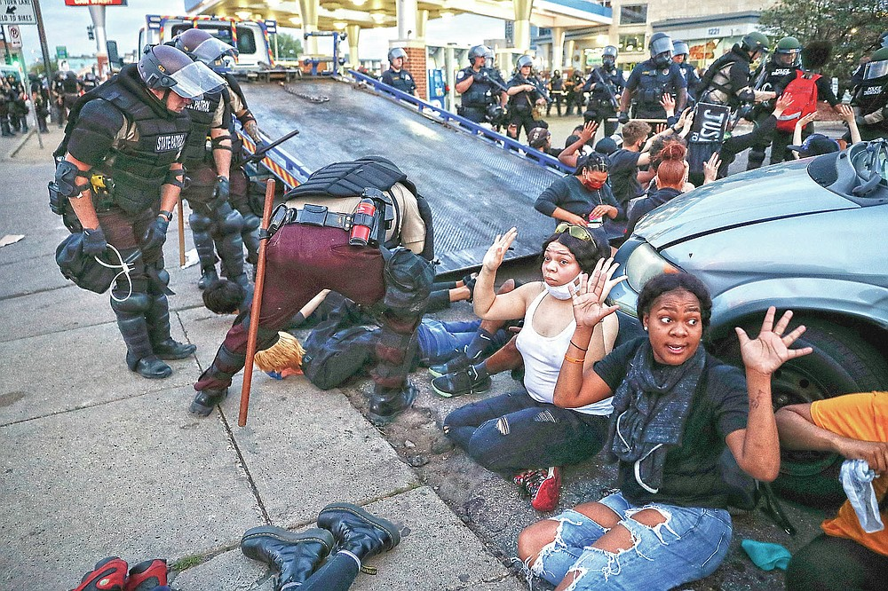 Protesters raise their hands on command from police as they are detained prior to arrest and processing at a gas station on South Washington Street, May 31, 2020, in Minneapolis. The image was part of a series of photographs by The Associated Press that won the 2021 Pulitzer Prize for breaking news photography. (AP Photo/John Minchillo)
