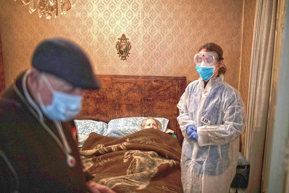 """Josefa Ribas, 86, who is bedridden, looks at nurse Alba Rodriguez as Ribas' husband, Jose Marcos, 89, stands by in their home in Barcelona, Spain, March 30, 2020, during the coronavirus outbreak. Ribas suffers from dementia, and Marcos fears for them both if the virus enters their home. """"If I get the virus, who will take care of my wife?"""" The image was part of a series by Associated Press photographer Emilio Morenatti that won the 2021 Pulitzer Prize for feature photography. (AP Photo/Emilio Morenatti)"""