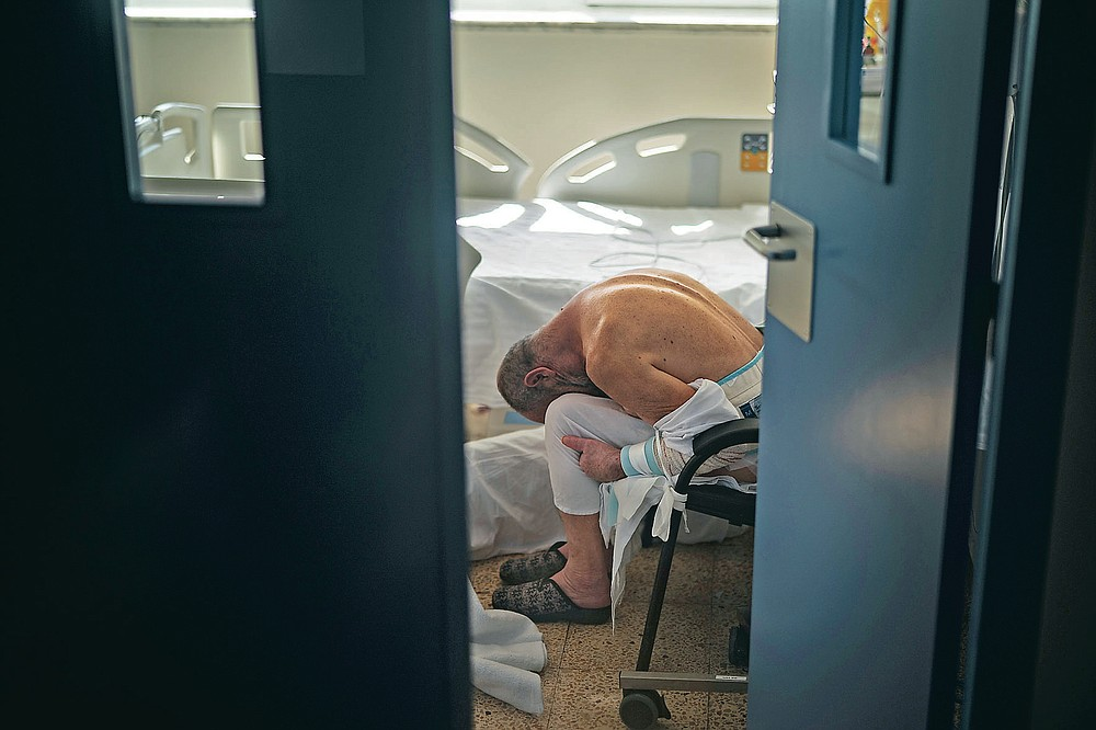 A patient infected with Coronavirus rests in a chair inside an isolated room at the COVID-19 ward of a public hospital in Barcelona, Spain, Nov. 18, 2020. The image was part of a series by Associated Press photographer Emilio Morenatti that won the 2021 Pulitzer Prize for feature photography. (AP Photo/Emilio Morenatti)