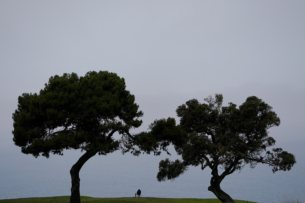 A marshal overlooks the Pacific Ocean from the fifth green during a practice round of the U.S. Open Golf Championship, Wednesday, June 16, 2021, at Torrey Pines Golf Course in San Diego. (AP Photo/Jae C. Hong)