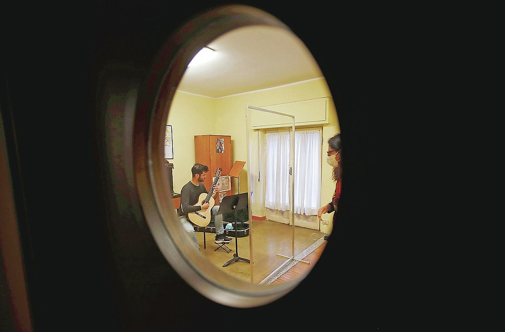 Carlo D'Ariano is seen through a window as he plays his guitar behind a transparent panel to curb the spread of COVID-19, during a lesson with maestro Maria Vittoria Jedlowski at the Giuseppe Verdi Music Conservatory, in Milan, Italy, Thursday, April 29, 2021. Whatever the instrument, flute, violin or drums, students at Italy's oldest and largest music conservatory have been playing behind plexiglass screens during much of the pandemic as the Conservatoryfound ways to preserve instruction throughout Italy's many rolling lockdowns. (AP Photo/Antonio Calanni)