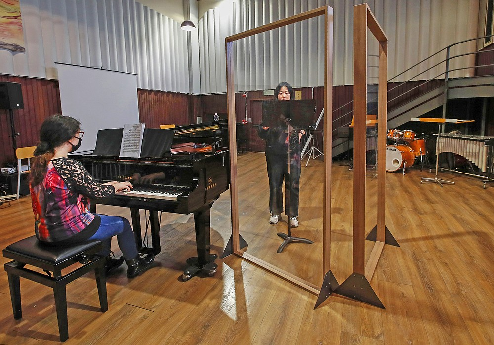 Ylenia Labanca, left, plays piano with a singer Yidan Fu, behind a transparent panel to curb the spread of COVID-19, during a lesson at the Giuseppe Verdi Music Conservatory, in Milan, Italy, Thursday, April 29, 2021. Whatever the instrument, flute, violin or drums, students at Italy's oldest and largest music conservatory have been playing behind plexiglass screens during much of the pandemic as the Conservatoryfound ways to preserve instruction throughout Italy's many rolling lockdowns. (AP Photo/Antonio Calanni)