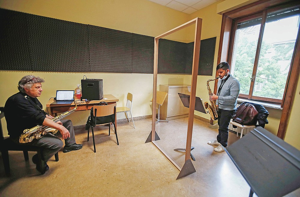 Luis Urgiles, right, plays his saxophone behind a transparent panel to curb the spread of COVID-19, during a lesson with maestro Tino Tracanna at the Giuseppe Verdi Music Conservatory, in Milan, Italy, Thursday, April 29, 2021. Whatever the instrument, flute, violin or drums, students at Italy's oldest and largest music conservatory have been playing behind plexiglass screens during much of the pandemic as the Conservatoryfound ways to preserve instruction throughout Italy's many rolling lockdowns. (AP Photo/Antonio Calanni) I