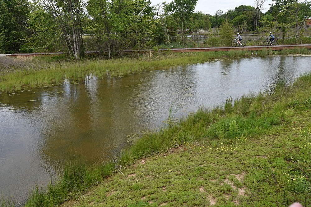 Bikers roll across the wetland near the Lake Bentonville spillway at Osage Park. (NWA Democrat-Gazette/Flip Putthoff)