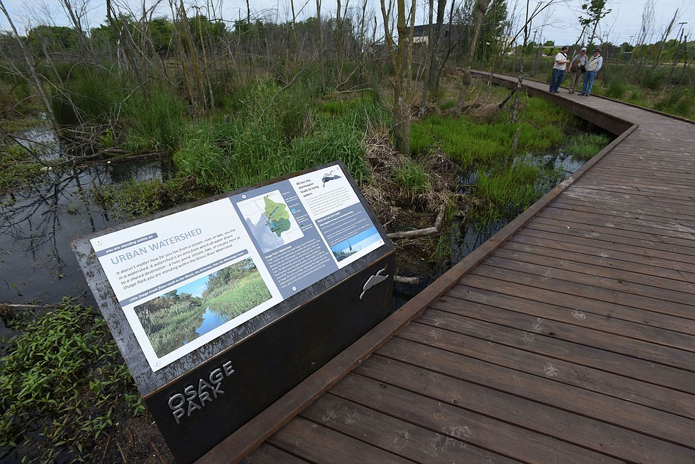 Interpretive signs explain features of the urban wetland. (NWA Democrat-Gazette/Flip Putthoff)