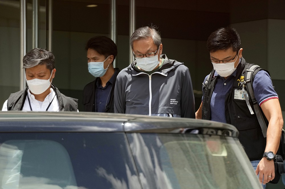 Police officers escort Cheung Kim-hung, right, CEO and Executive Director of Next Digital Ltd at Apple Daily headquarters in Hong Kong, Thursday, June 17, 2021. Hong Kong police on Thursday morning arrested the chief editor and four other senior executives of Apple Daily under the national security law on suspicion of collusion with a foreign country to endanger national security, according to local media reports. (AP Photo/Kin Cheung)